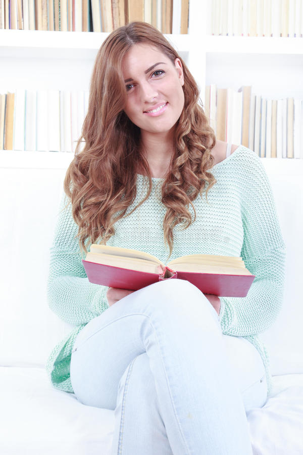 Woman reading a book while sitting on a white couch in a living. Room with library background behind her, domestic atmosphere stock photos