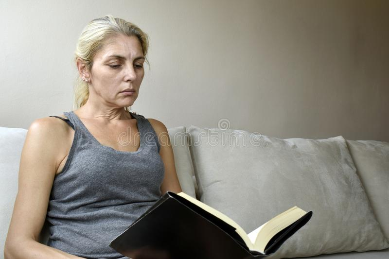 Woman reading book on sofa stock photo