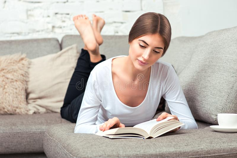 Woman reading a book on sofa royalty free stock image