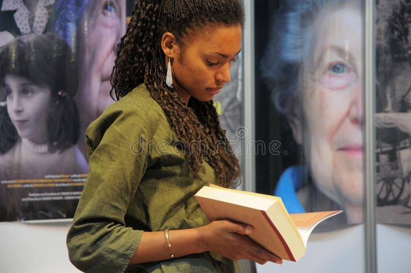 Woman reading a book standing close view royalty free stock image
