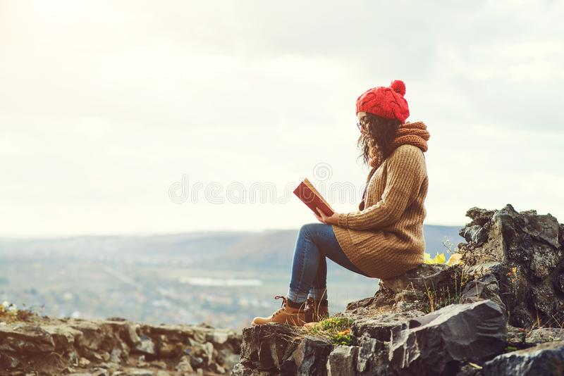 Woman reading book on the top of rock in autumn day. royalty free stock photo