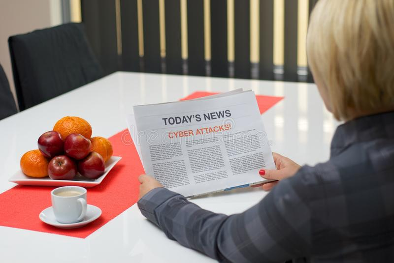 Woman reading about cyber attacks. Woman reading cyber attack article in the newspaper at home royalty free stock image