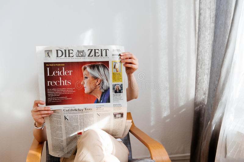 Woman reading Die Zeit with Marine Le Pen on cover. PARIS, FRANCE - APR 24, 2017: Marine Le Pen on newspaper cover - woman reading the German Die Zeit newspaper stock image