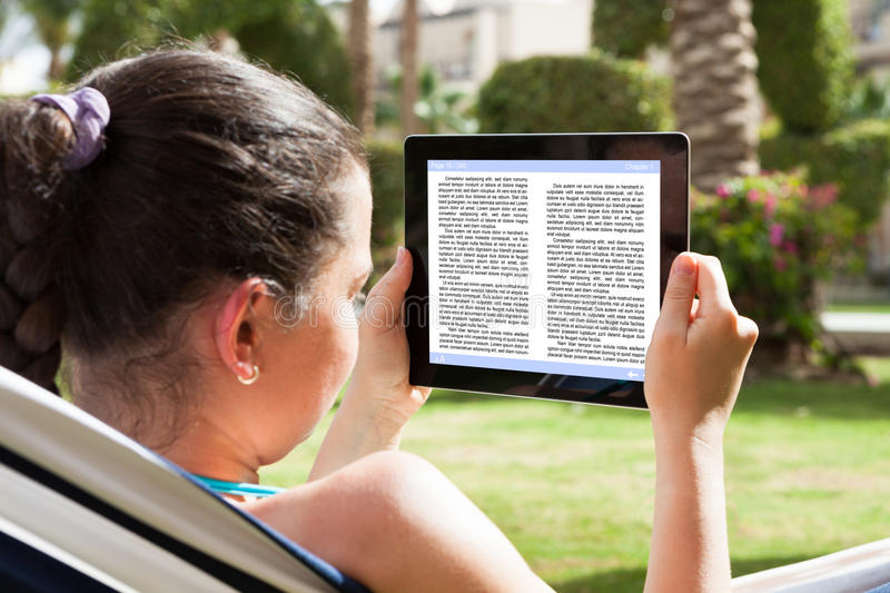 Woman reading ebook. Closeup Of A Young Woman Reading Ebook royalty free stock photo