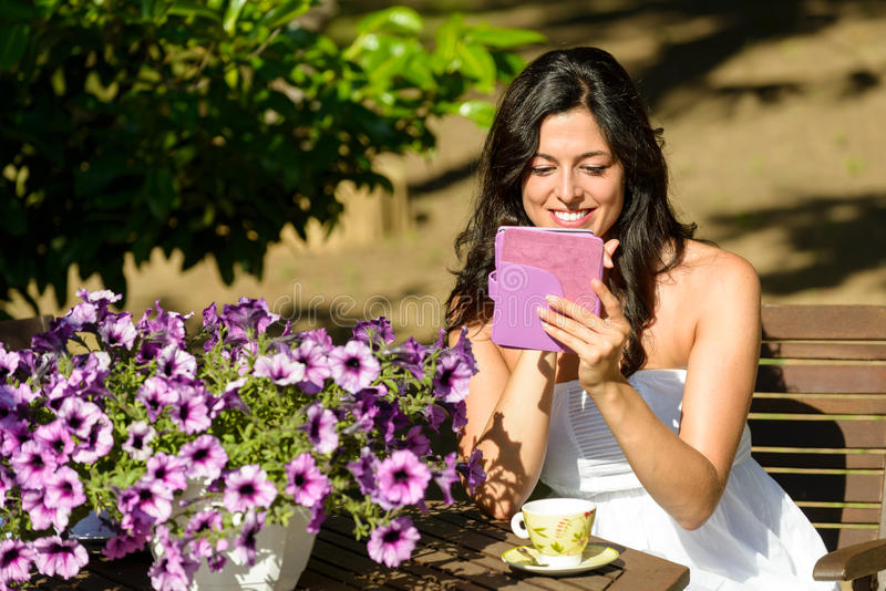 Woman reading ebook in garden. Woman reading novel on ebook and enjoying morning breakfast on summer in garden. Female reader and electronic book stock images