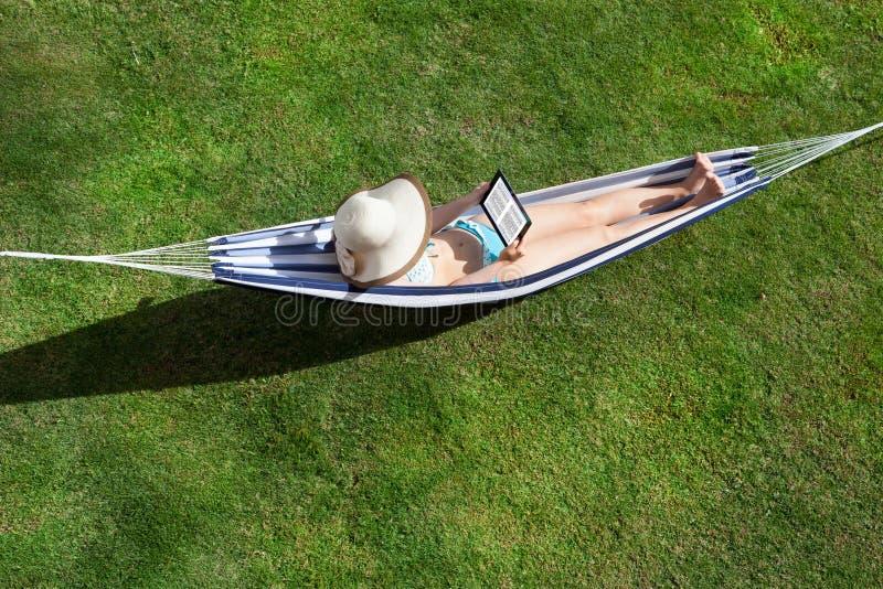 Woman reading ebook lying in hammock stock image