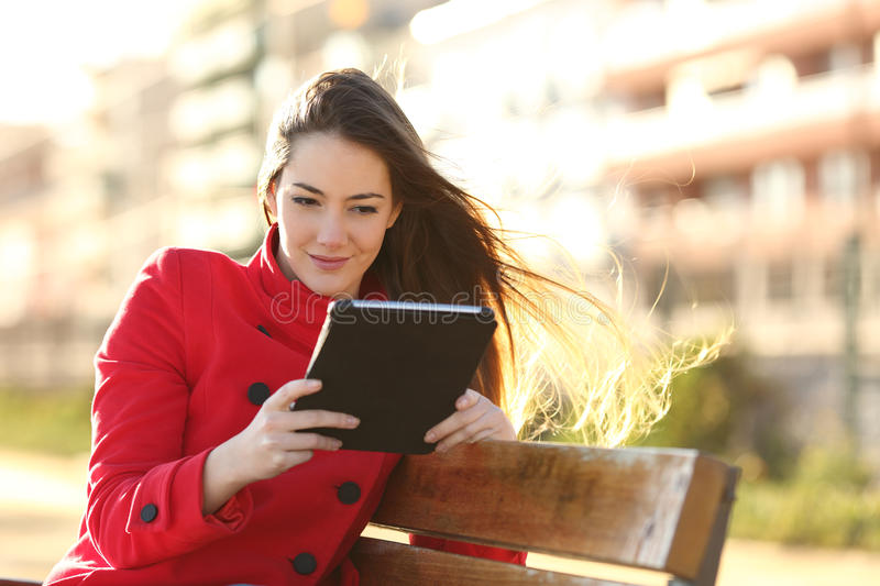 Woman reading an ebook or tablet in an urban park. With buildings in the background stock photos