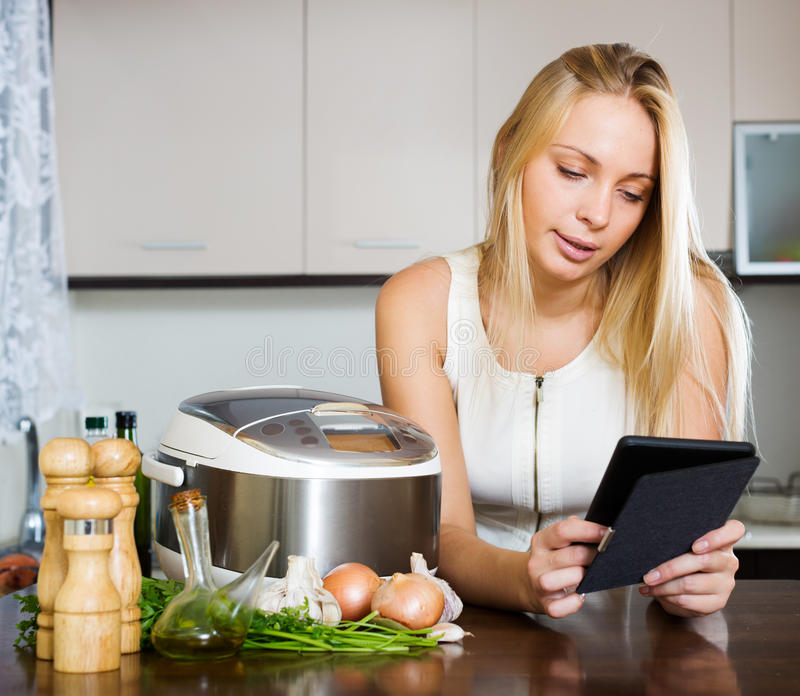 Woman reading ereader and cooking with crockpot royalty free stock images