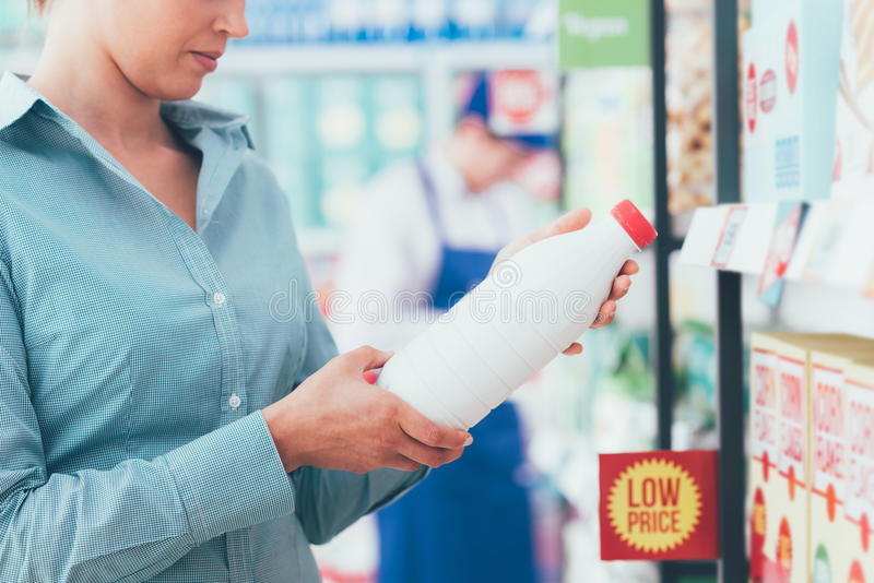 Woman reading food labels. Woman doing grocery shopping at the supermarket and reading food labels, nutrition and quality concept stock photo