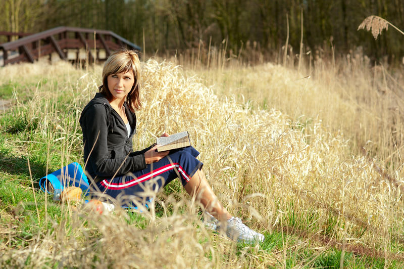 Woman Reading on Grass. Woman sitting on grass reading a book stock photography