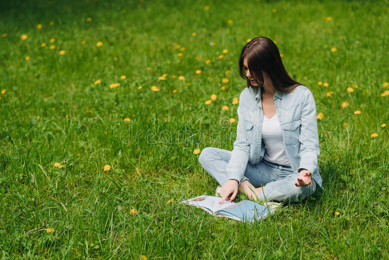Woman reading on grass in park. Beautiful young woman reading a book on grass with dandelion flowers in park stock image