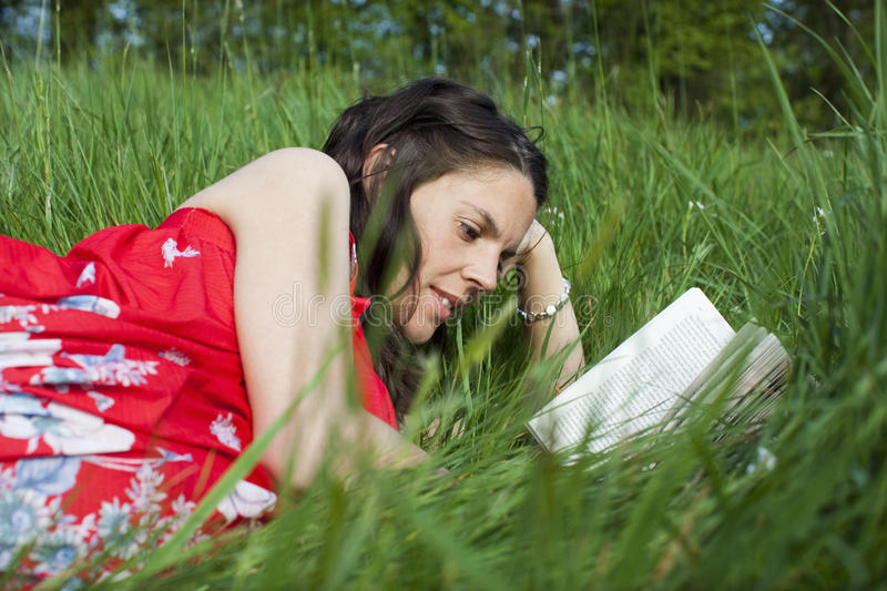 Woman Reading On Grass. Young woman lying on grass and reading stock images