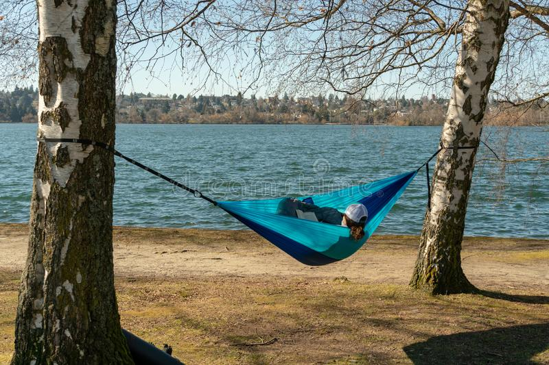 Woman reading in hammock. Seattle, Washington - 2019-03-17 - Woman reading a book in a hammock hanged from a couple of trees in Greenlake as Spring begins in stock photo
