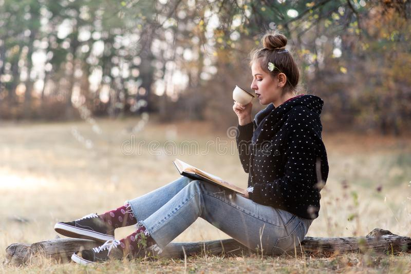 Woman reading and having a cup of coffee outdoors stock photography