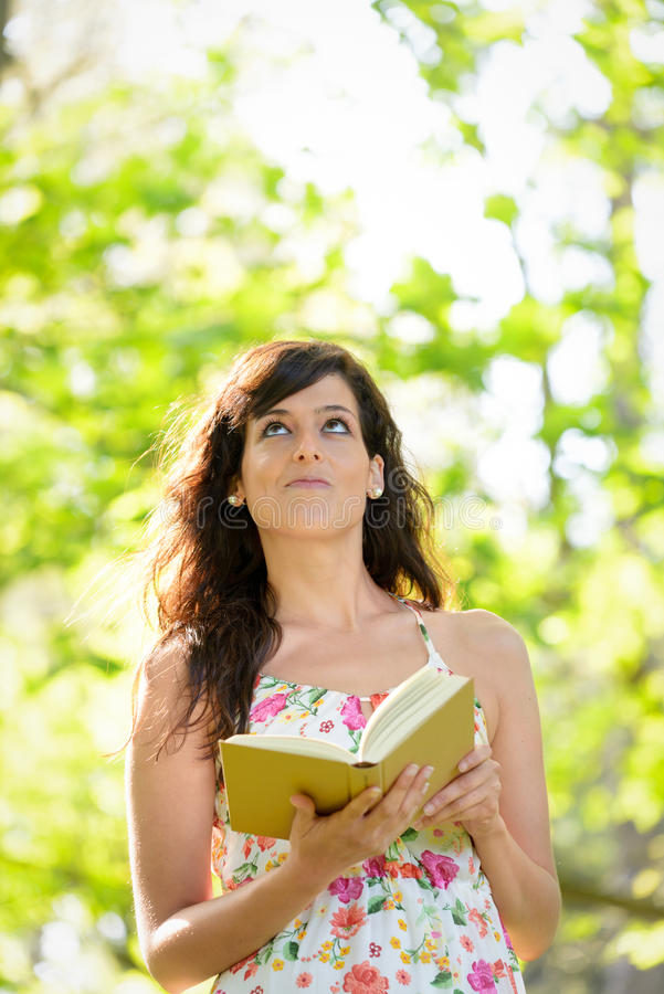 Woman reading and having idea royalty free stock photography