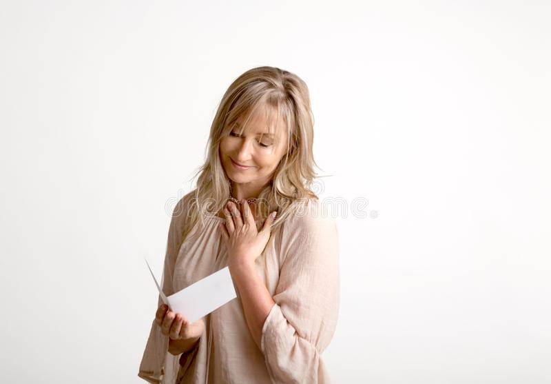 Woman reading a heartfelt message note or card royalty free stock photography