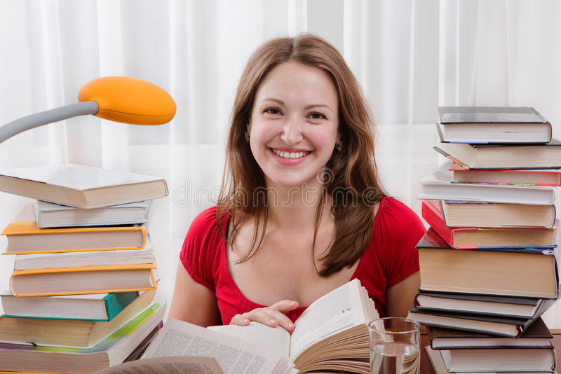 Woman reading her book for school. Studying happy young woman reading her book for school. Woman seating at the table with books. Smiling female student is royalty free stock photos