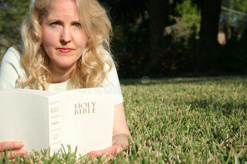 Woman reading holy bible in gr royalty free stock photography