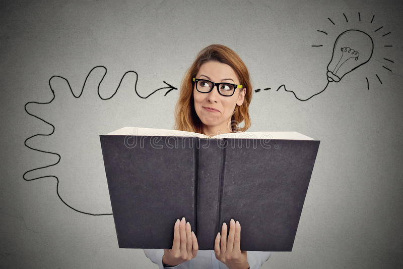 Woman reading a huge book has a good idea. Portrait young woman reading a huge book has a good idea royalty free stock image
