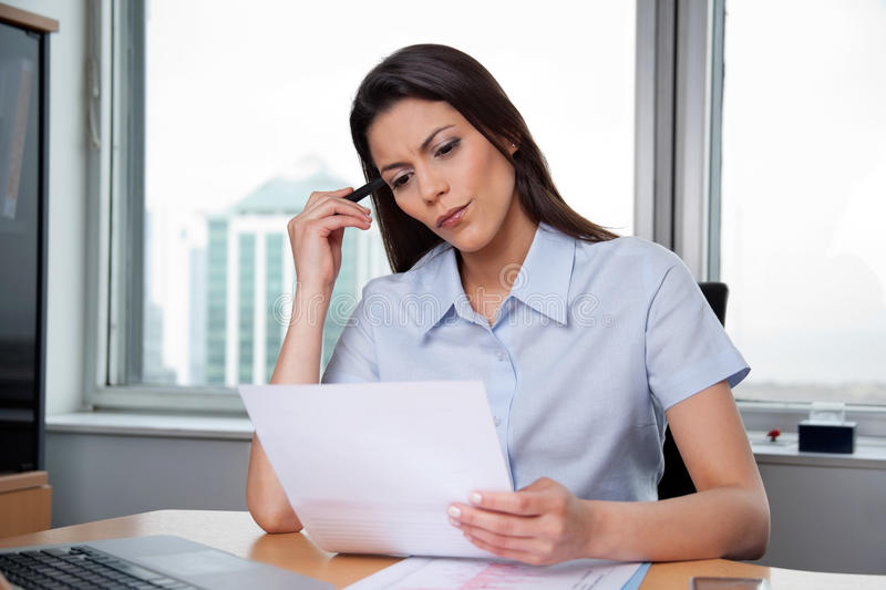 Woman Reading Important Business Papers. Thoughtful businesswoman reading important business papers stock images
