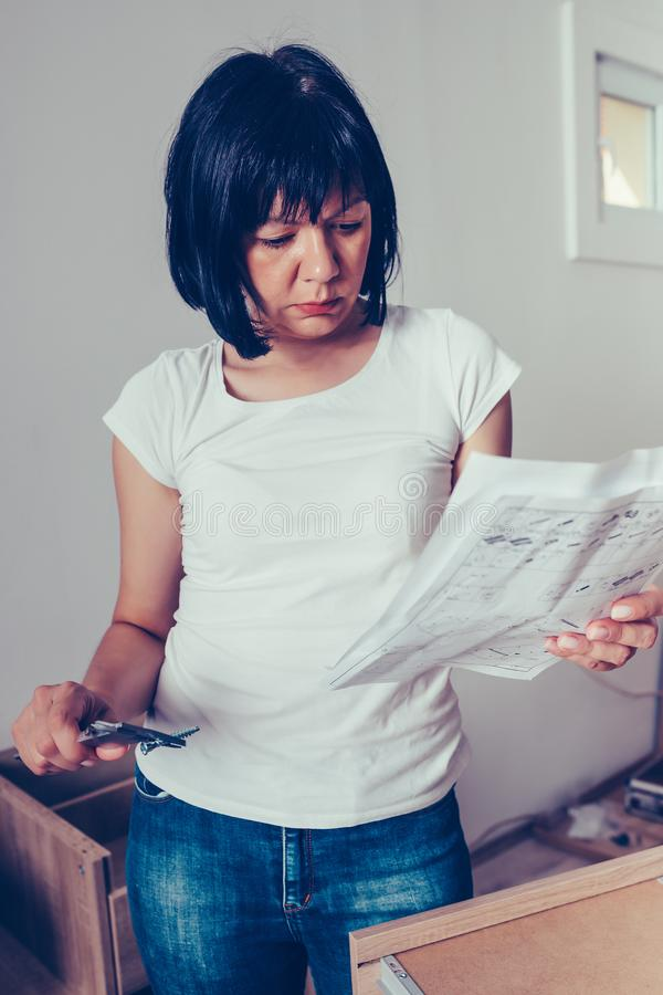 Woman is reading instruction for installation furniture and checking screw size with caliper royalty free stock photo