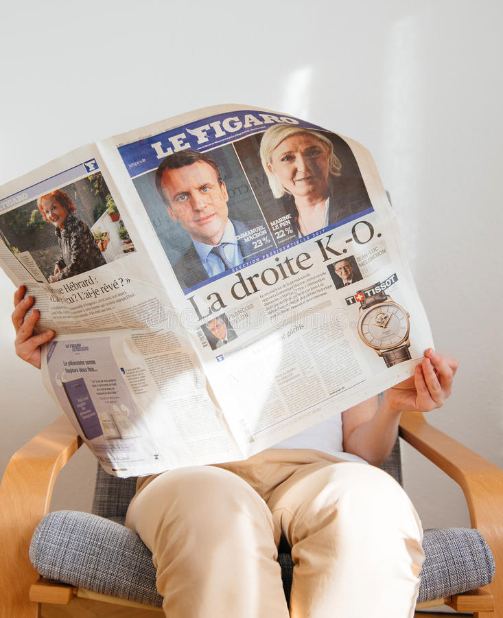 Woman reading Le Figaro with Emmanuel Macron and Marine Le Pen o. PARIS, FRANCE - APR 24, 2017: Emmanuel Macron on newspaper cover - woman reading the French royalty free stock photos