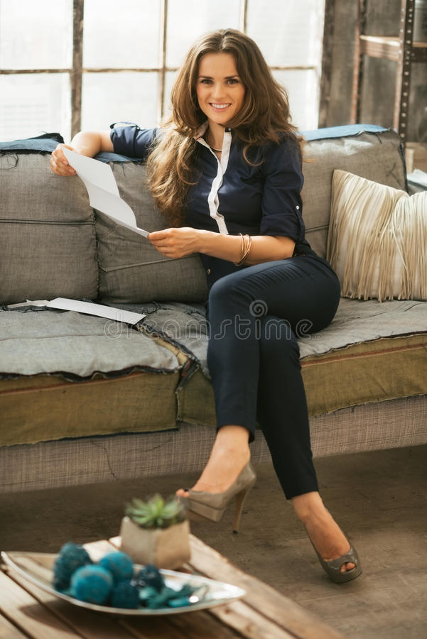 Woman reading letter in loft apartment royalty free stock photography