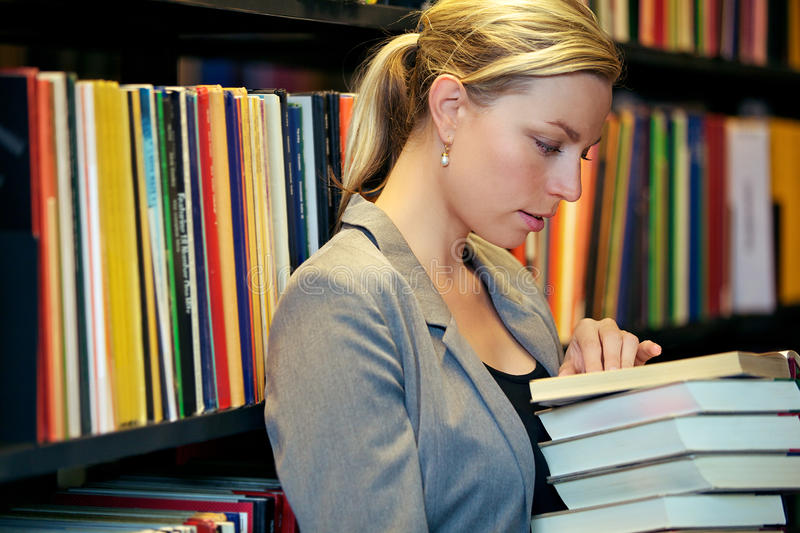 Download Woman reading in a library stock photo. Image of concentrating - 26480534