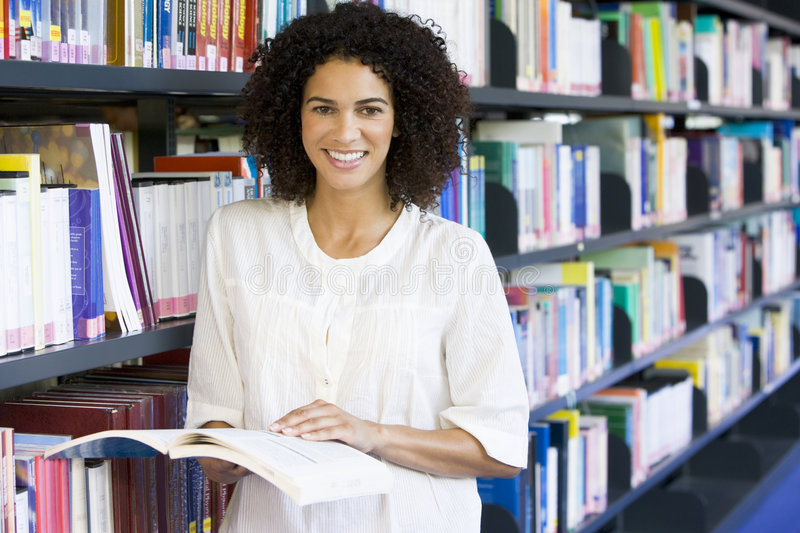 Woman reading in a library royalty free stock photos