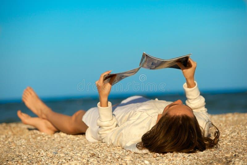 Woman reading magazine on beach. Beach scene. Young woman reading magazine stock image