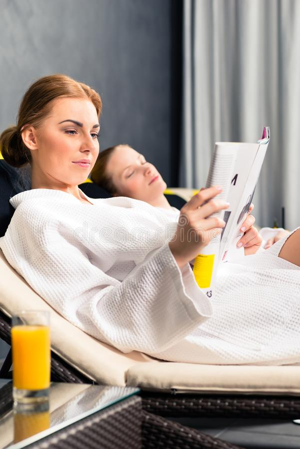 Woman reading magazine book in spa stock images