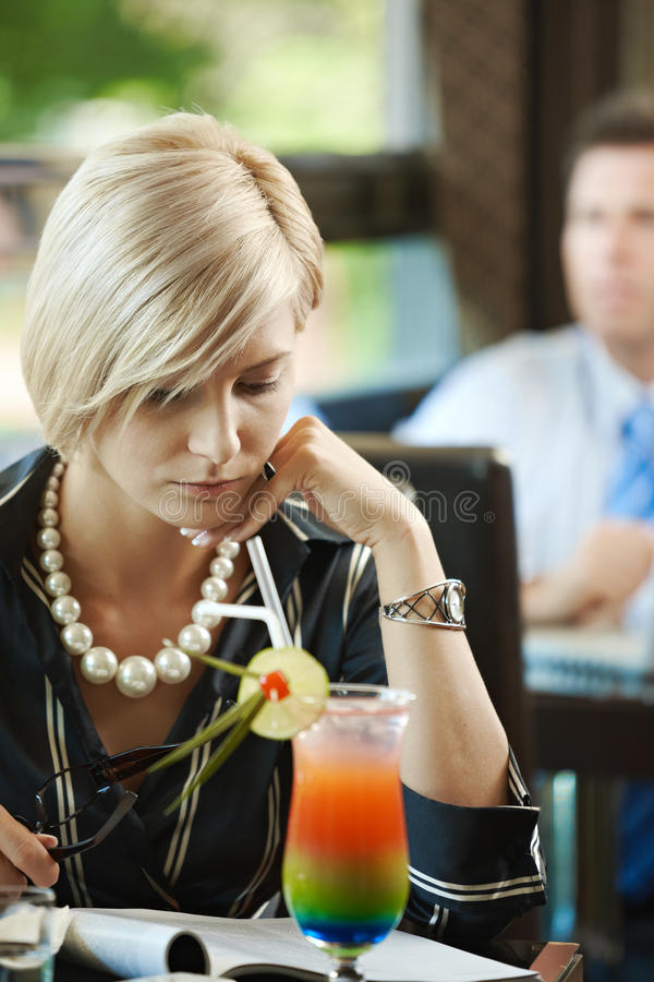 Woman reading magazine in cafe stock image