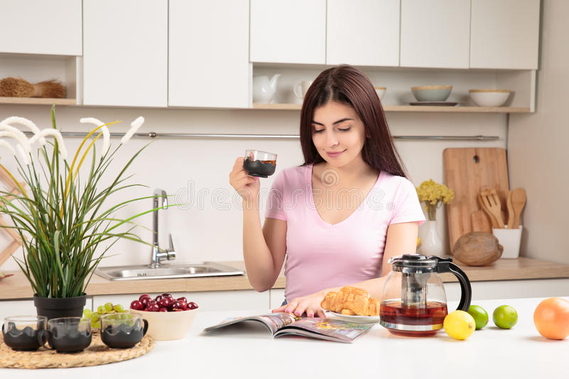 Woman Reading Magazine and drinking tea In Kitchen royalty free stock images