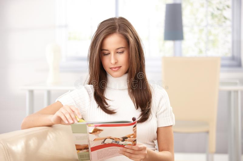Woman reading magazine at home stock image