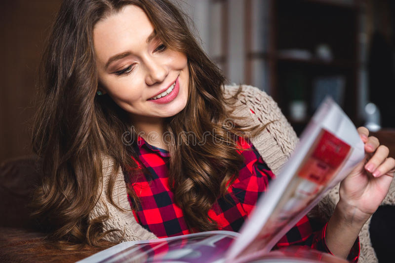 Woman reading magazine at home stock photo