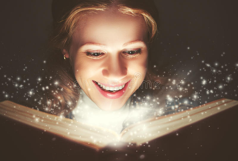 Woman reading a magic book. Glowing in the dark royalty free stock photo