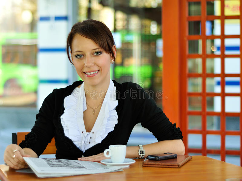 Woman reading news at the cafe stock images