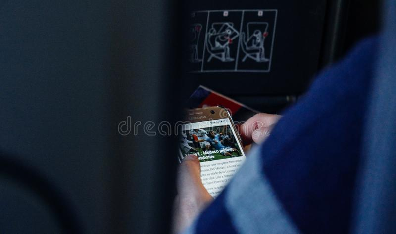 Woman reading news on smartphone on the airplane using wi-fi stock photos