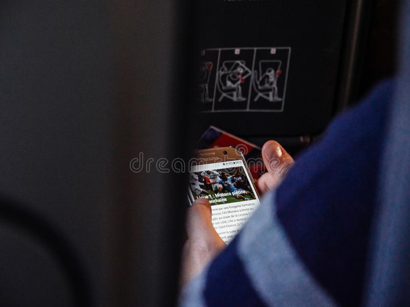 Woman reading news on smartphone on the airplane using wi-fi stock images