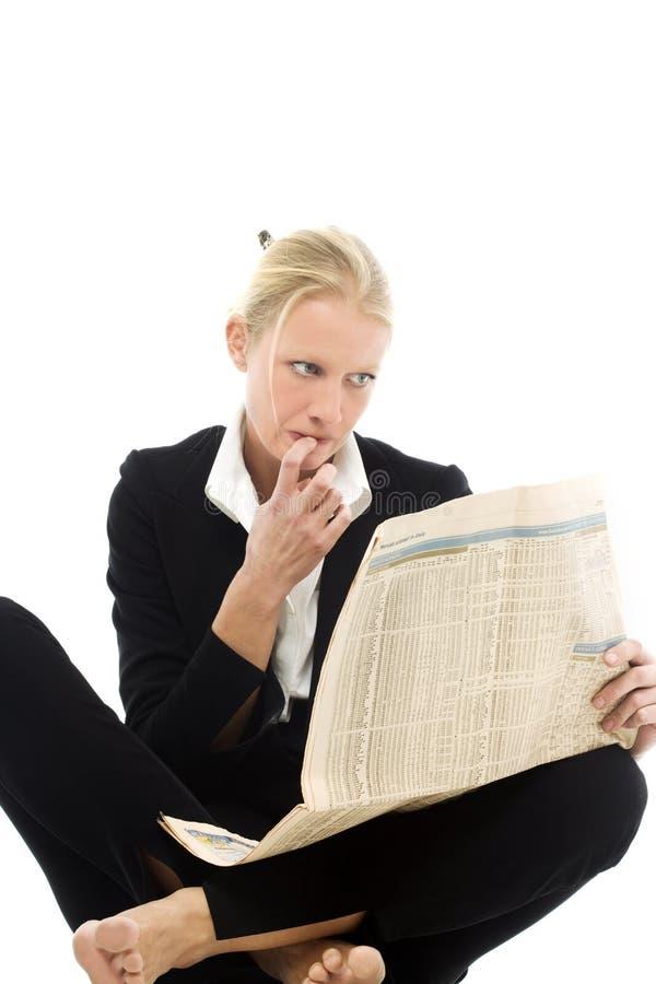 Woman reading newspaper stock image