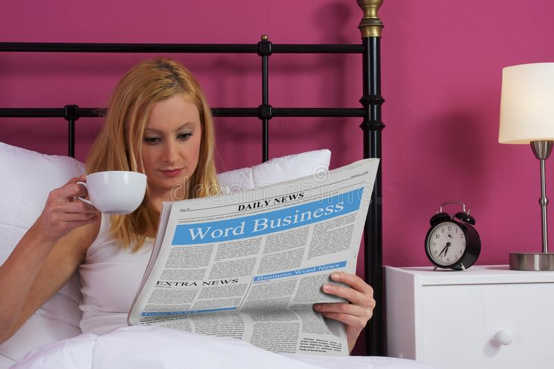 Woman reading newspaper in bed royalty free stock image