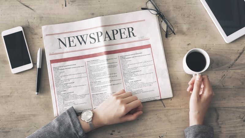 Woman reading newspaper and drinking coffee on table royalty free stock photography