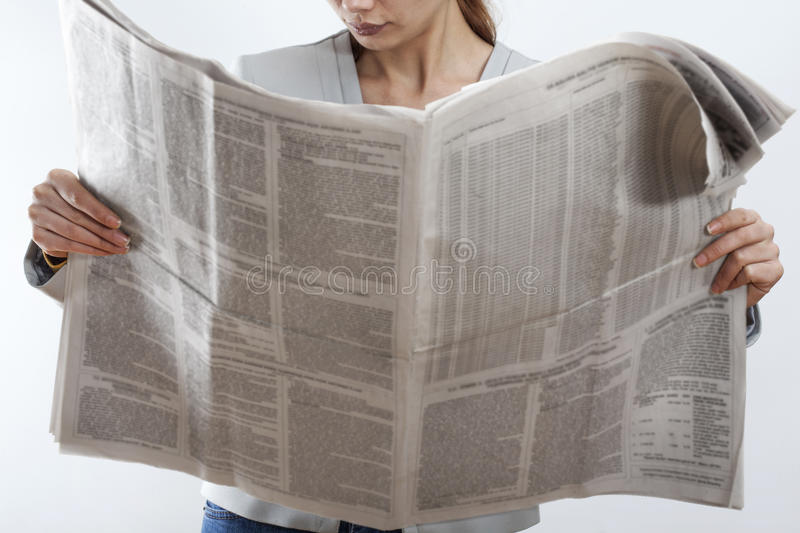 Woman reading newspaper on white background stock photography