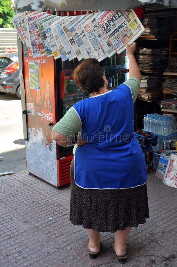 Woman reading newspapers stock images