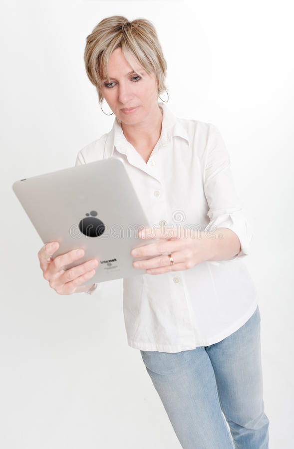 Woman Reading From A PC Tablet Stock Images