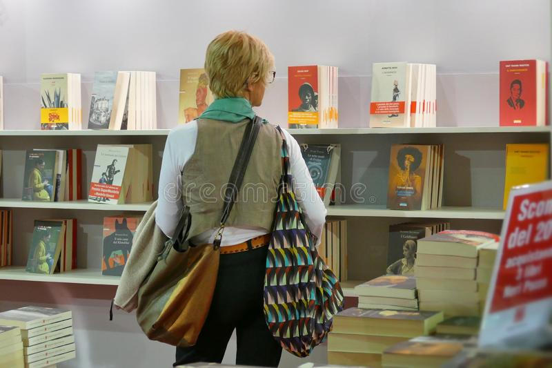 Woman reading and picking books in library store of international book fair stock photos