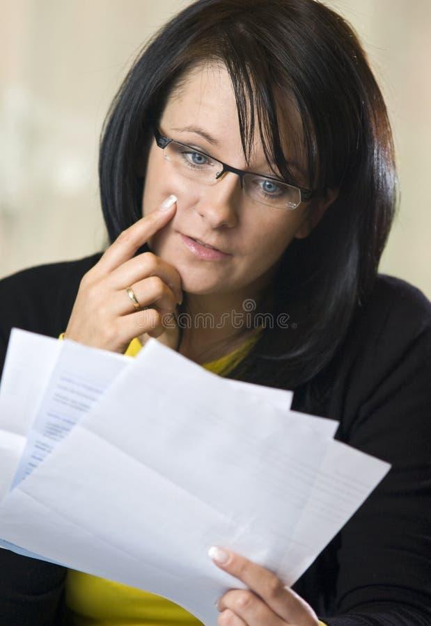 Woman reading pile of bills stock image