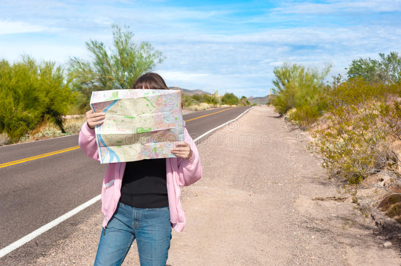 Woman reading roadmap. A woman stands along side a remote deserted road reading a map royalty free stock photos