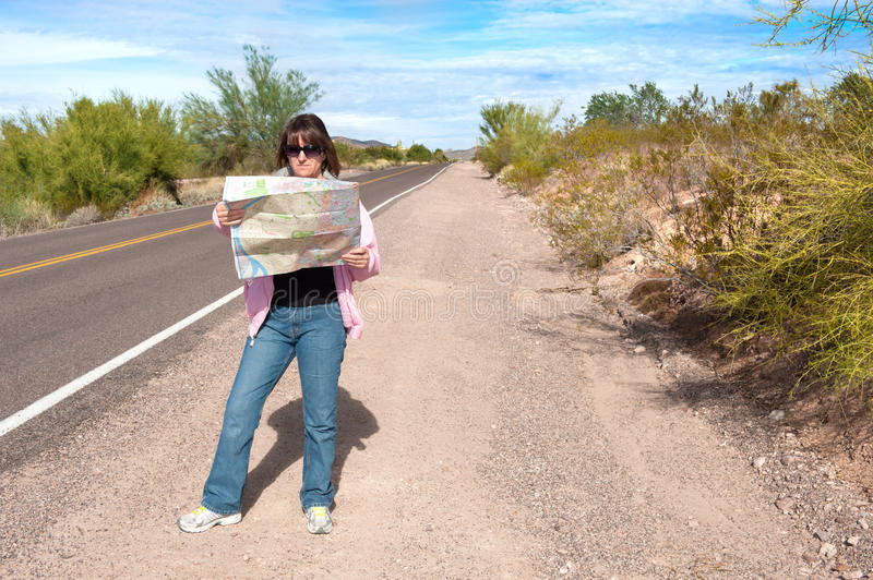 Woman reading roadmap. A woman stands along side a remote deserted road reading a map stock image