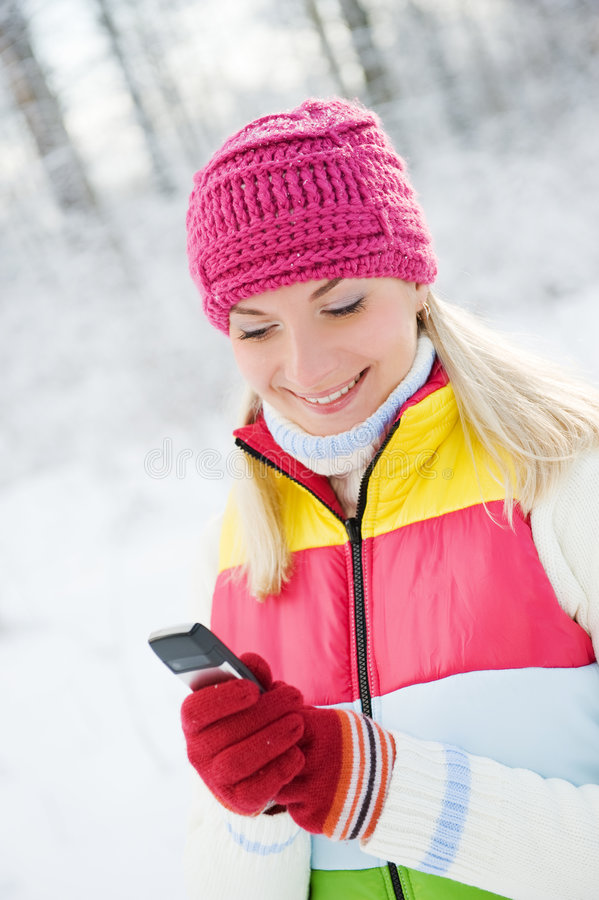 Woman reading sms. Beautiful young woman reading sms on her cellular phone stock photo